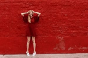 Pretty woman in red shirt standing next to red wall